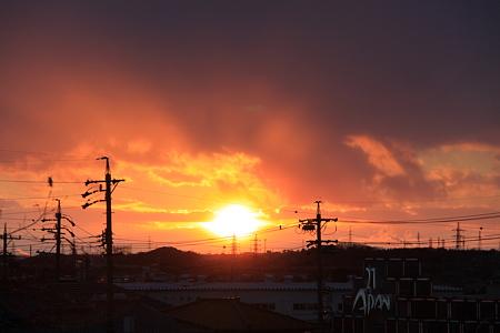 小雪舞う中の燃えるたぎる夕陽