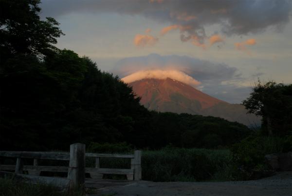日の出前の暗さの中で朝日を浴びて光る富士山
